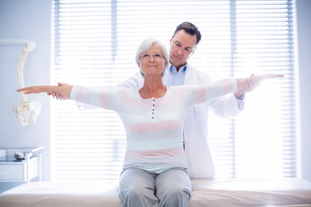 Physiotherapist giving hand massage to senior woman
