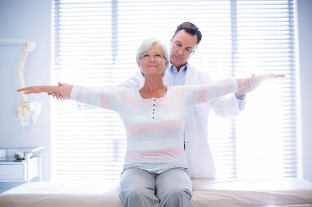 年配の女性にハンドマッサージを与える理学療法士
