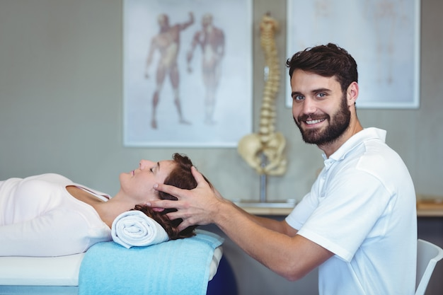 Physiotherapist giving head massage to a woman