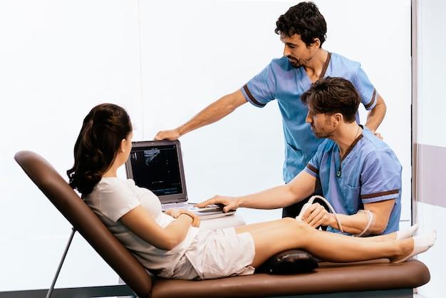 クリニックの女性に膝の治療を行う理学療法士。理学療法の概念