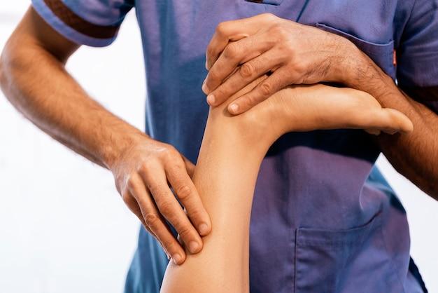 클리닉에서 여성에게 무릎 치료를 제공하는 물리 치료사. 물리 치료 개념