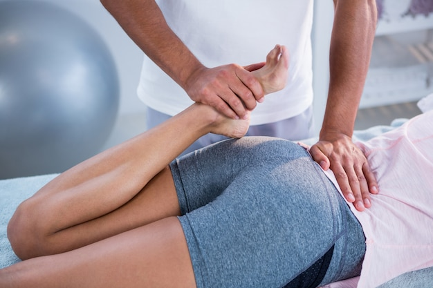 女性に脚マッサージを与える理学療法士