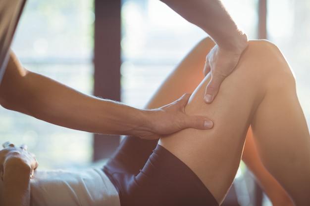 Physiotherapist giving leg massage to a woman