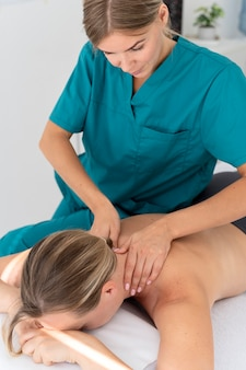 Physiotherapist giving a massage to her patient at the clinic