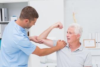 Physiotherapist giving massage to senior man