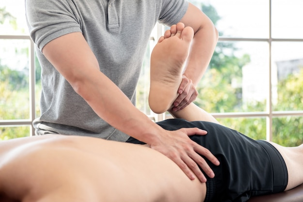 Physiotherapist giving massage and stretching to athlete male patient