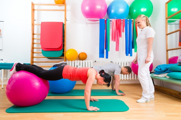Physiotherapist giving patients gymnastic exercise