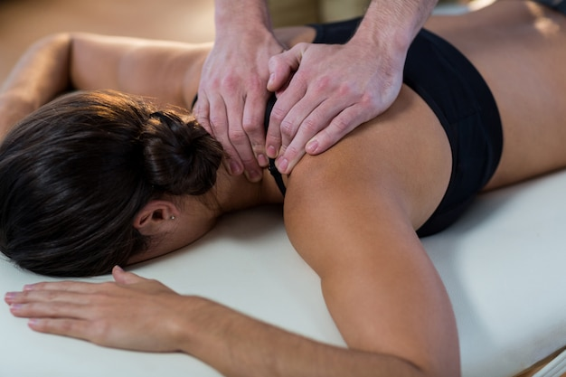 Physiotherapist giving physical therapy to the neck of a female patient