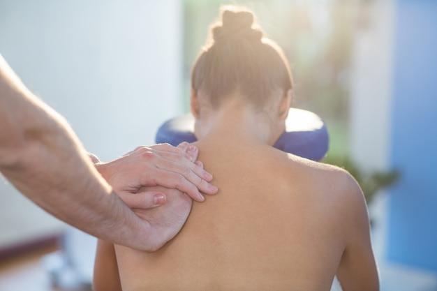 女性患者に肩のマッサージを与える理学療法士