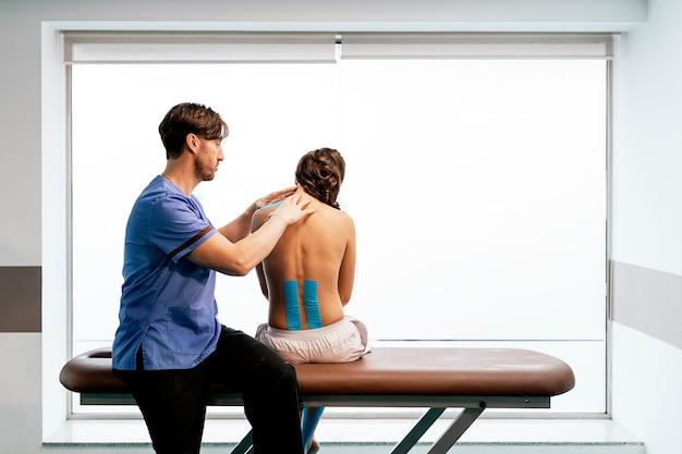 Physiotherapist giving shoulder therapy to a woman in clinic. physical treatment concept