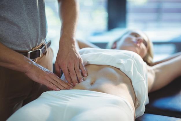 女性に胃のマッサージを与える理学療法士