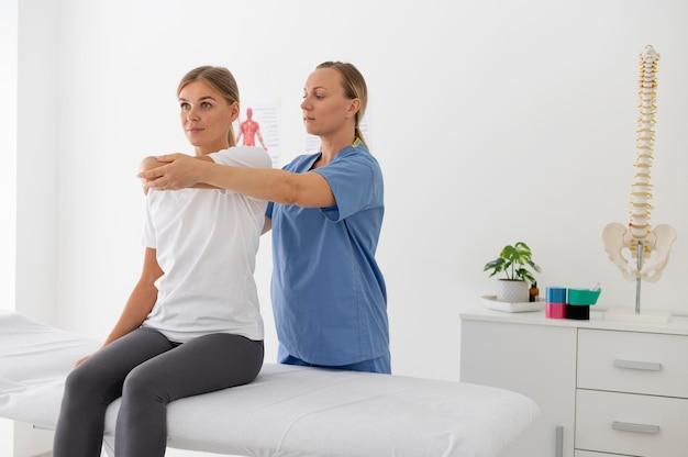 그녀의 클리닉에서 여성 환자를 돕는 물리 치료사