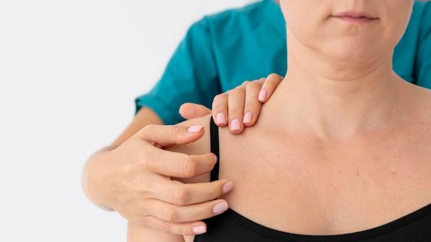 Физиотерапевт помогает пациенту в ее клинике