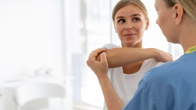 그녀의 클리닉에서 젊은 여성 환자를 돕는 물리 치료사