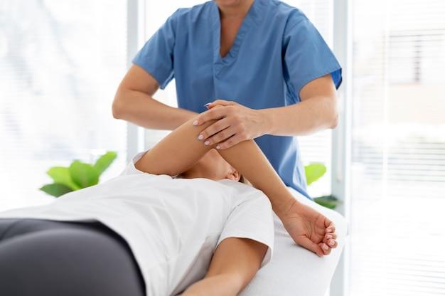 젊은 여성 환자를 돕는 물리 치료사