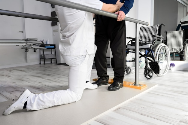 Physiotherapist helping disabled caucasian senior man to walk with parallel bars in rehabilitation center.