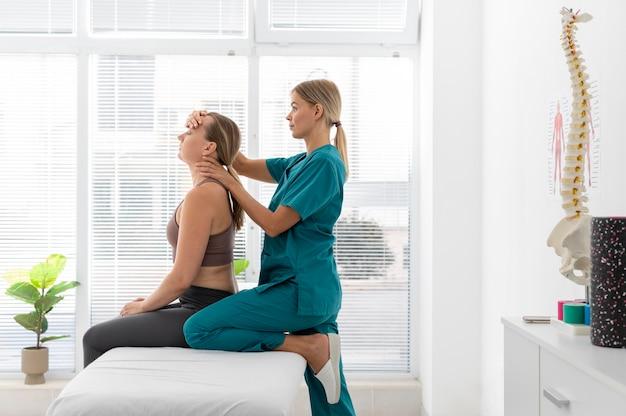 Fisioterapista che aiuta un paziente nella sua clinica