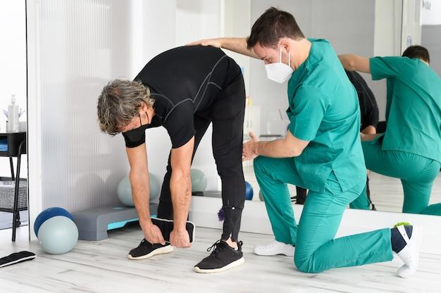 Физиотерапевт помогает пациенту в клинике.