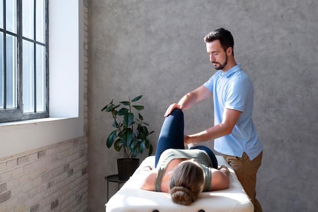 환자의 중간 샷을 돕는 물리 치료사