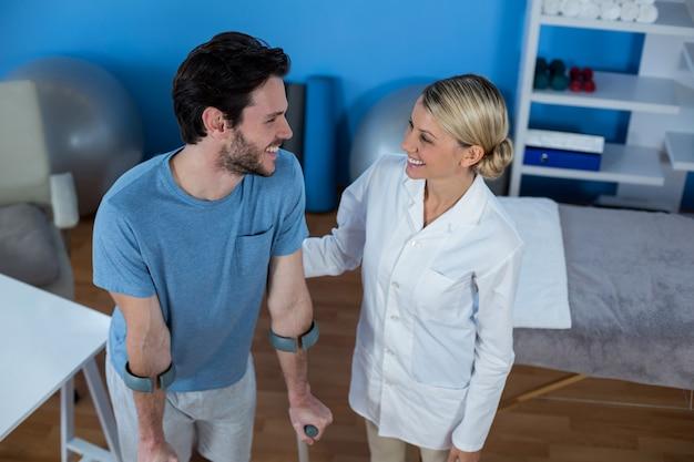 Физиотерапевт помогает пациенту ходить на костылях