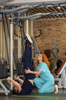 Physiotherapist helps patient to rehabilitate