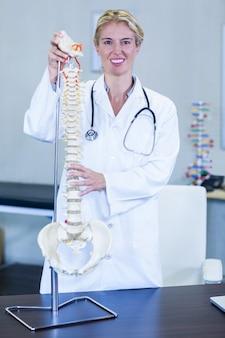 脊椎モデルを保持している理学療法士