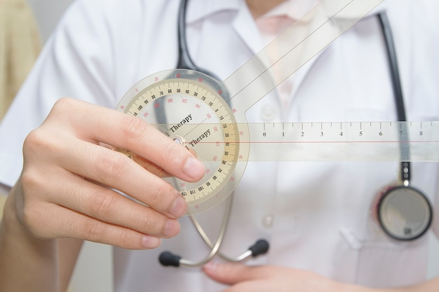 Physiotherapist  holding  a goniometer for measuring range of motion