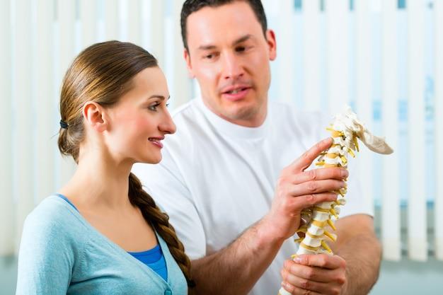彼の診療における理学療法士は、女性患者の脊柱と腰痛の出現について説明しています
