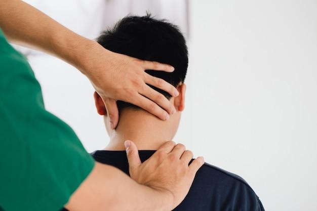 남성 고객의 머리를 잡고 단단한 목 근육을 마사지하는 물리 치료사 마사지 치료사