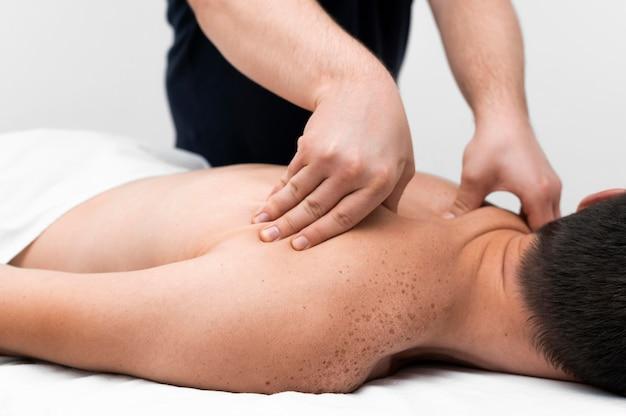 Физиотерапевт, массируя спину пациента мужского пола