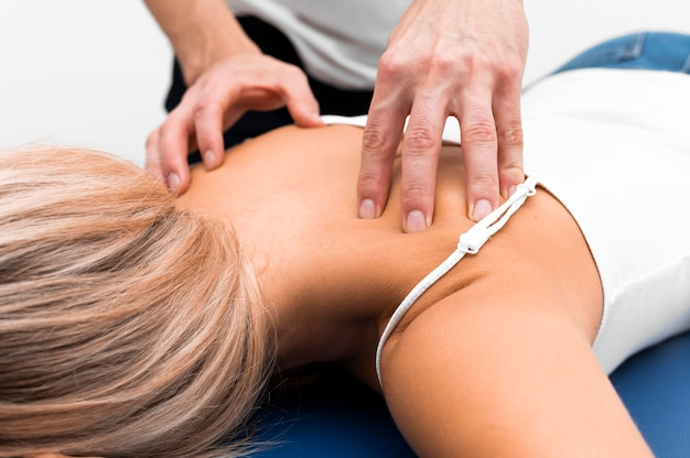 Physiotherapist massaging female patient's back for pain