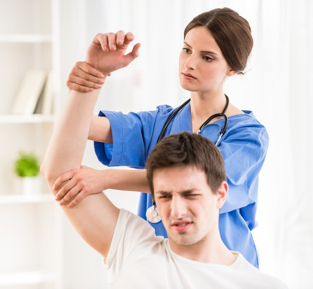 Physiotherapist massaging the hand of male patient.