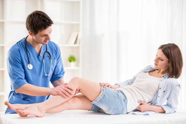 Physiotherapist massaging the leg of female patient.