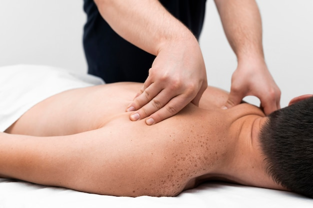 Physiotherapist massaging a male patient's back