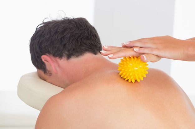 Physiotherapist massaging male patient with yellow massage ball