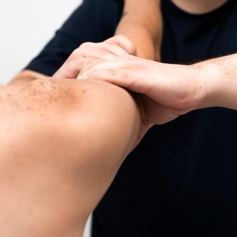 Physiotherapist massaging man's arm
