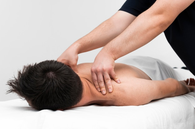 Physiotherapist massaging man's back
