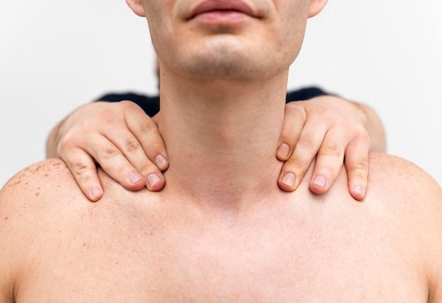 Physiotherapist massaging man's neck