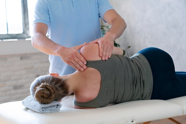 Physiotherapist massaging patient close up