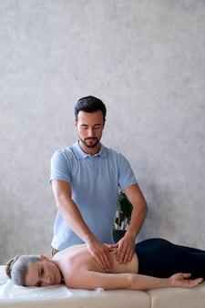 Physiotherapist massaging woman medium shot