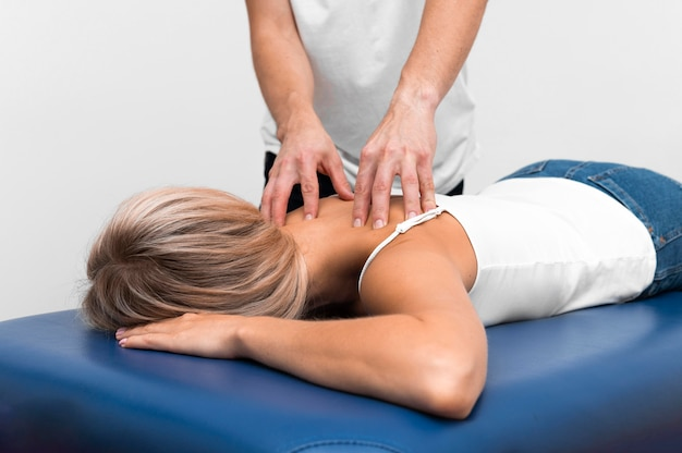 Physiotherapist massaging woman's back for pain
