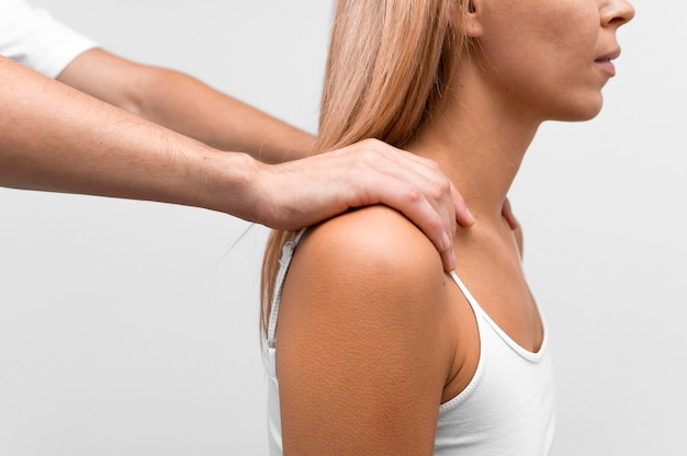Physiotherapist massaging woman's shoulder
