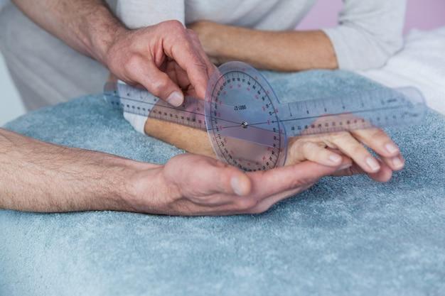 理学療法士がゴニオメーターで患者の手を測定