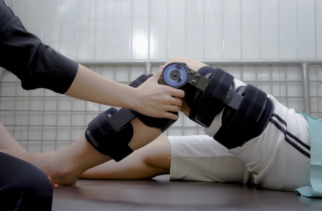Physiotherapist measuring range of motion on patients' knee with goniometer