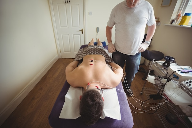 Physiotherapist performing electro dry needling on the back of a patient