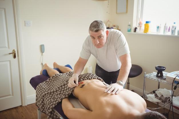Fisioterapista che esegue aghi elettro-asciutti sul paziente