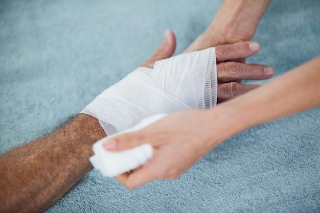 理学療法士が患者の負傷した手に包帯を置く