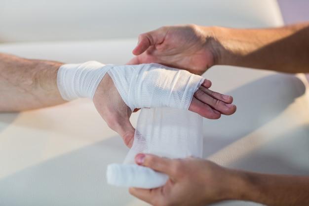 男性患者の手に包帯を置く理学療法士