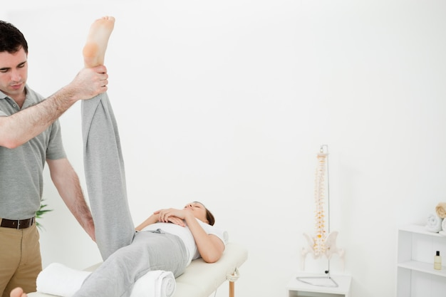 Physiotherapist raising the leg of a woman
