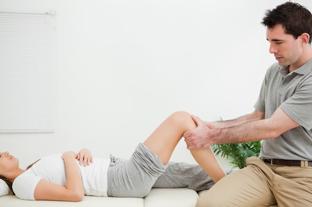 Physiotherapist sitting while massaging a knee